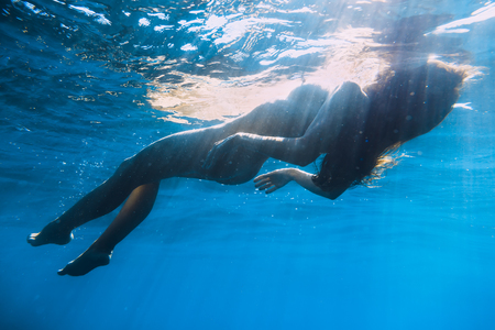 Young naked woman relaxed in ocean, underwater