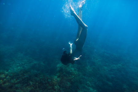 Young naked woman dive in the ocean, underwater
