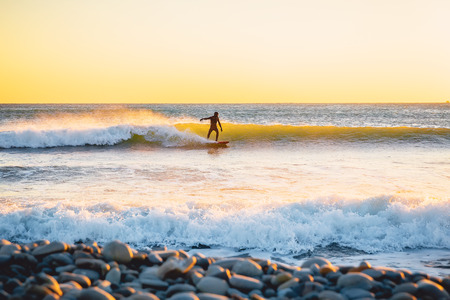 Surfer on wave at warm sunset. Surfing in the ocean Stock Photo