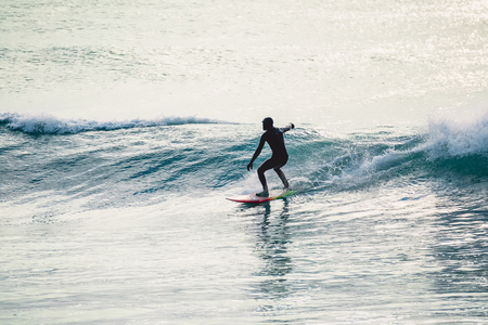 Surfer ride on wave. Winter surfing in ocean Stock Photo - 93120555