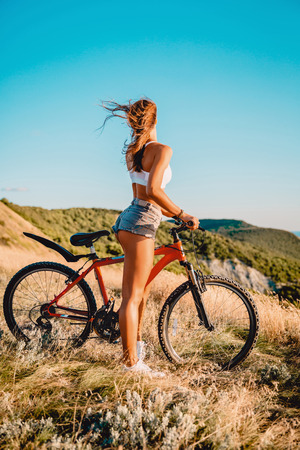 Young active girl with mountain bicycle in white shirt, shorts and white sneakers outdoor