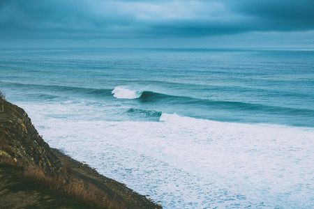 Crashing big wave in ocean and cloudy weather. Ideal waves for surfing