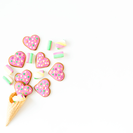 Gingerbread cookies made with pink glaze and marshmallow in waffle cone on withe background. Holiday food concept. Flat lay. top view.