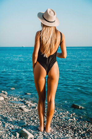 Attractive woman in black bikini with bonnet relaxing at sea