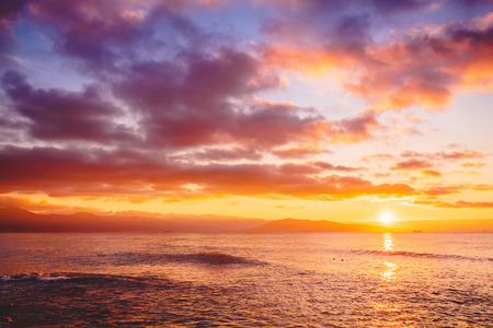 Bright sunset or sunrise in the ocean. Landscape with warm sunset or sunrise colors