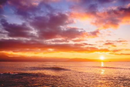 Brillante puesta de sol o amanecer en el océano. Paisaje con cálidos colores del atardecer o del amanecer. Foto de archivo