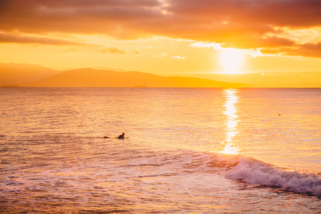 Surfer in the ocean at warm sunset or sunrise. Winter surfing in ocean
