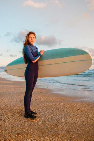 Young surfer woman with surfboard on a beach at warm sunset or sunrise. Stock Photo