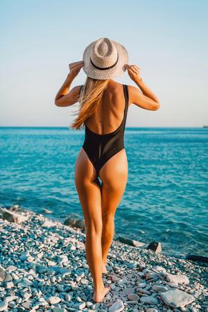 Attractive woman in black bikini with bonnet at sea