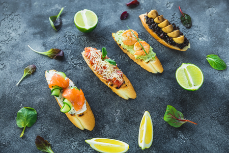 Sandwiches with prawn, salmon, mushroom and limes on dark background. Restaurant food