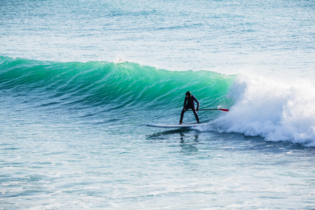 Surfer ride on stand up paddle board on ocean waves. Stand up paddle boarding in the ocean