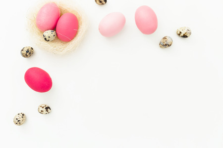 Easter eggs and quail eggs in nest on white background, Top view, Fat lay. Easter holiday concept with copy space