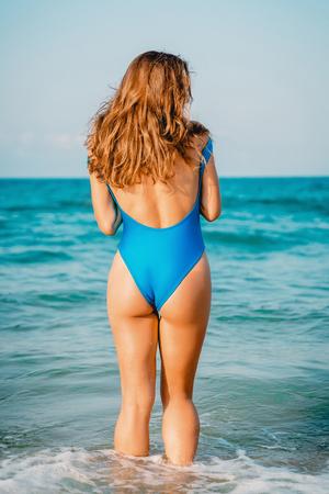 Attractive tan woman in blue bikini on ocean. Tropical vacations Stock Photo