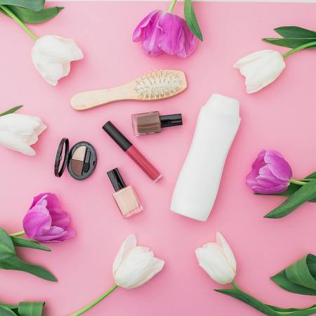 Beauty concept with shampoo, combs, cosmetics and flowers on pink background. Flat lay, top view