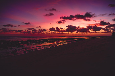 Bright colorful sunset or sunrise at ocean with clouds in Bali