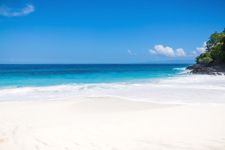 Tropical white sand beach and blue ocean with crystal water in Bali