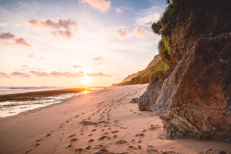 Tropical beach with rocks and sunset or sunrise colors