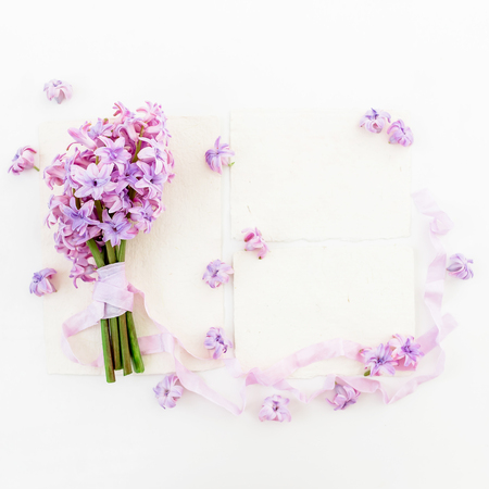 Bouquet of pink hyacinth flowers and tapes with cards on white background. Flat lay, top view.