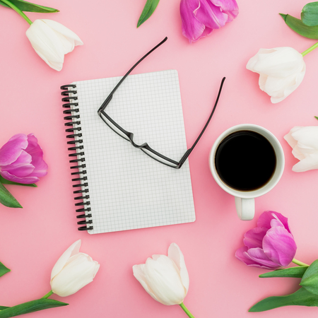 Tulips flowers with coffee mug, notebook and glasses on pink background. Blogger concept. Flat lay, top view.