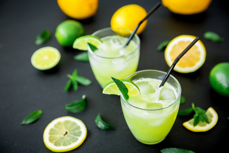 Refreshing lemonade in glass with limes, lemons