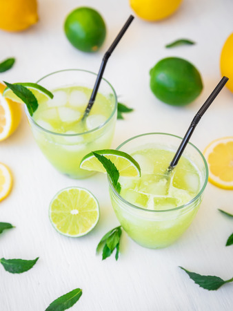 Citrus lemonade with limes, mint and lemons in glass on white table