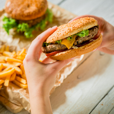 Hands hold american burger and french fries, sauce on a wooden plate