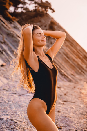 Attractive smiled woman in stylish swimwear on stones beach with warm sunset colors.