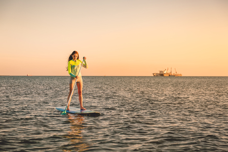 Sporty young girl stand up paddle surfing with beautiful sunset colors