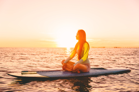 Stand up paddle boarding on a quiet sea with warm sunset colors. Relaxing on ocean Stock Photo