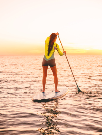 Sporty young woman standing up paddle surfing with beautiful sunset or sunrise colors Stock Photo
