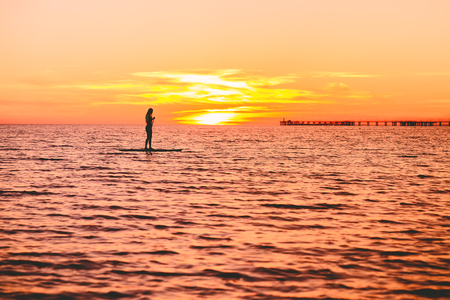 Woman standing up paddle boarding at dusk on a quiet sea with beautiful sunset