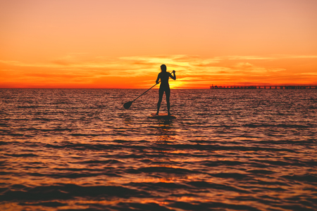 Surfer woman standing up paddle boarding at dusk on a flat warm sea with beautiful sunset colors Stock Photo