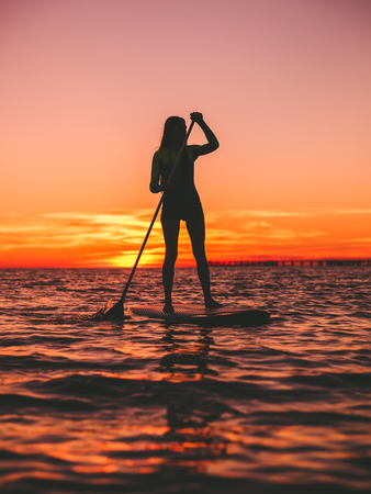 Woman standing up paddle boarding at dusk on a flat warm sea with beautiful sunset