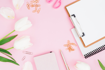 Frame of white tulips, clipboard, clips and scissors on pink background. Blogger concept. Flat lay, top view.