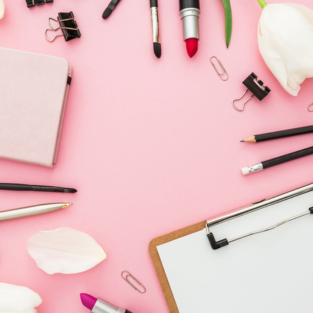 Business composition with clipboard, tulips, cosmetics and accessory on pink background. Top view. Flat lay. Home feminine desk. Stock Photo
