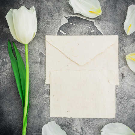 Floral composition with white tulips and paper envelope with card on dark background. Flat lay, top view. Floral pattern background. Stock Photo