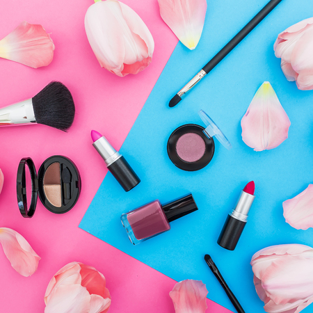 Beauty composition with tulips flowers and cosmetics on bright background. Top view. Flat lay, home feminine desk.
