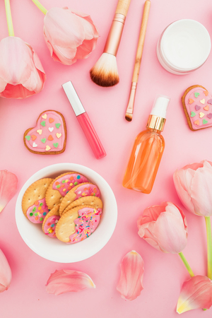 Pastel tulips flowers and cosmetics, cookies on pink background. Flat lay, top view. Stock Photo