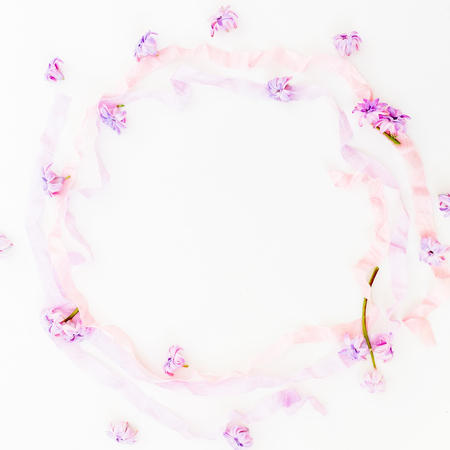 Purple frame made of pink hyacinth flowers and pastel tapes on white background. Flat lay, top view.