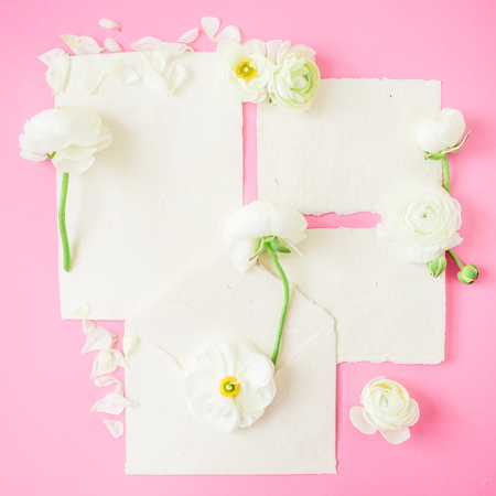 Composition with white flowers, petals and paper cards on pink background. Flat lay, top view. Vintage background. Stock Photo