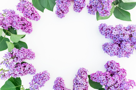 Floral frame with lilac flowers and leaves on white background. Flat lay, top view. Flower pattern