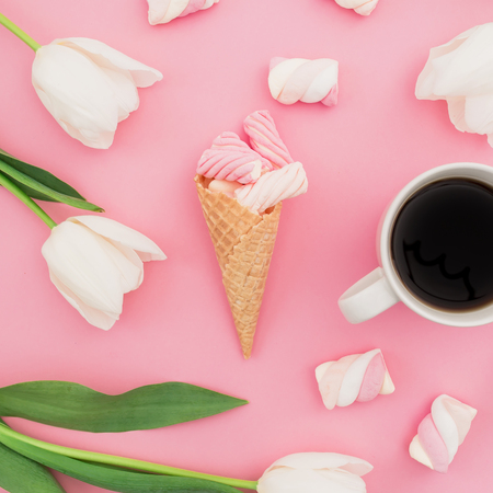 Tulips flowers with coffee mug, marshmallows and waffle cones on pink background. Flat lay, top view.