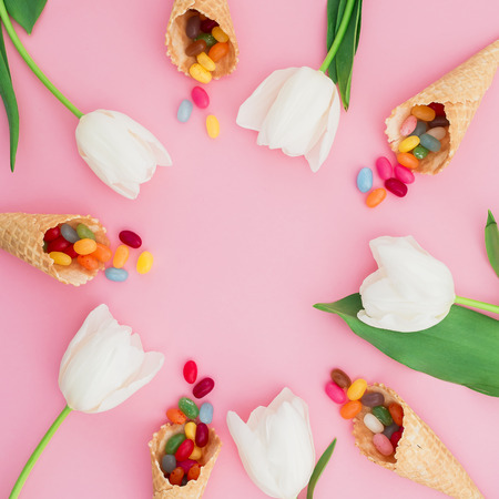 Frame made of sugar candy in waffle cones and white tulip flowers on pink background. Flat lay, top view Stock Photo