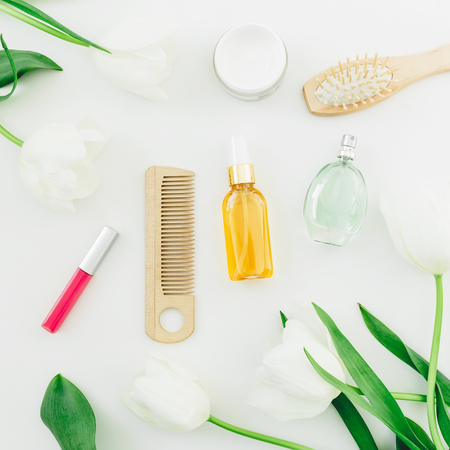 Cosmetic, perfume, combs and tulips flowers on white background. Beauty composition. Flat lay, top view