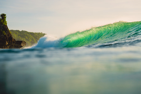 Breaking green wave in ocean. Perfect wave and evening light