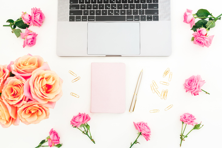 Silver laptop, dairy, roses flowers, marshmallow and accessories on white background. Flat lay. Top view. Freelancer office concept Stock Photo