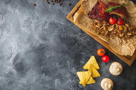 Grilled pork ribs, buckwheat with mushroom and tomatoes on vintage wooden cutting board on dark table. Flat lay, top view. Copy space. Stock Photo