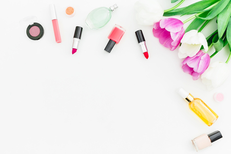 Frame with tulips flowers and cosmetics with perfume on white background. Top view. Flat lay. Copy space Stock Photo