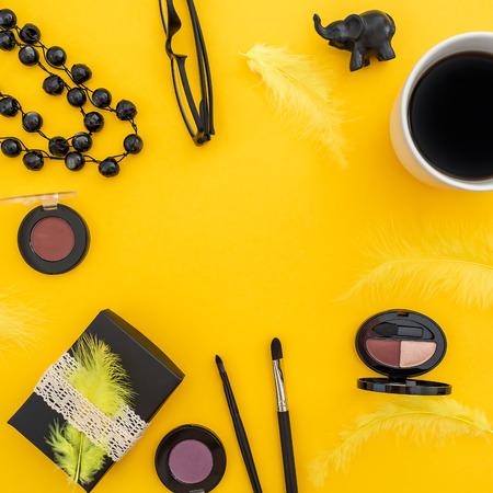 Round frame with gift box, glasses, cosmetics, bijouterie and accessories with mug of coffee on yellow background. Flat lay, top view. Stock Photo