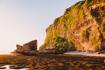High cliff with rocks, stones, low tide ocean and sunset colors in Bali